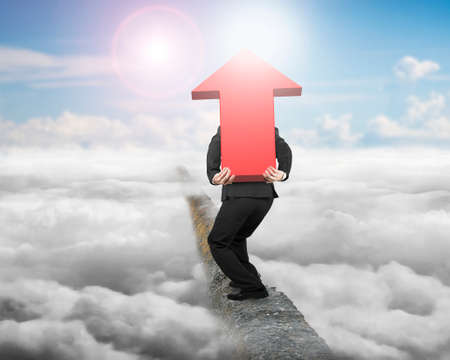 hard work ahead: Businessman carrying big 3D red arrow sign balancing on concrete ridge with sky sunlight cloudscape background