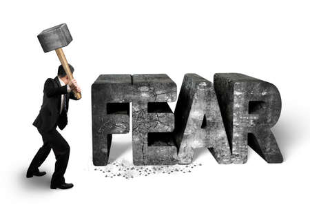 Businessman holding sledgehammer hitting 3d fear mottled concrete word isolated on white background, overcoming fear concept.