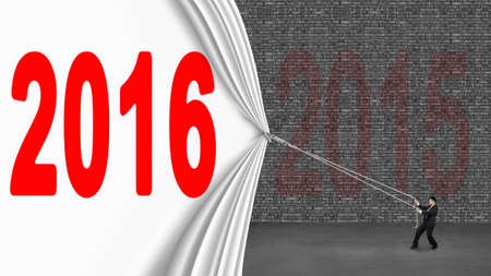 turns of the year: Businessman pulling down 2016 curtain covering old 2016 brick wall on gray concrete floor