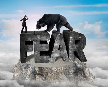 Businessman against black bear standing on fear 3D mottled concrete word, on top of mountain peak with sunny sky clouds background
