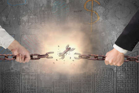 tug: Businessman pulling rusty iron chains broken with red bright spark light on gray doodles concrete wall background, tug of war, business competitive concept.