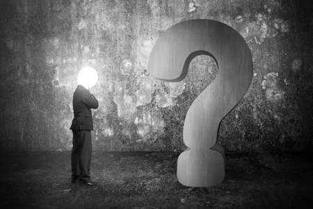 Thinking businessman with lamp head illuminated 3d concrete question mark and dark mottled wall background photo