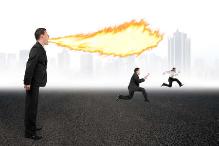 spitting: Angry businessman yelling at employees and spitting fire flame from mouth on asphalt floor and urban scene skyline background