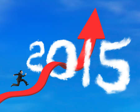 unstoppable: Businessman running on red arrow upward bending trend line breaking through 2015 shape clouds and blue sky background