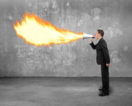 spitting: Angry businessman screaming into megaphone spitting fire flame with concrete indoor background Stock Photo