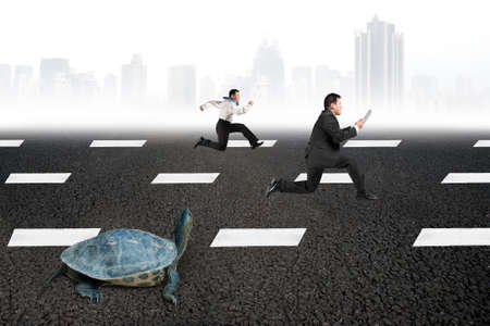 competition success: Two businessmen running with turtle on asphalt road with gray urban scene skyline background. Tortoise race competing metaphor concept.
