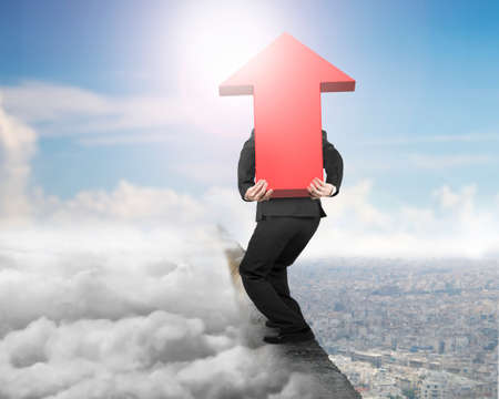 hard work ahead: Man carrying big 3D red arrow sign balancing on concrete ridge with sky cloudscape cityscape sunlight background