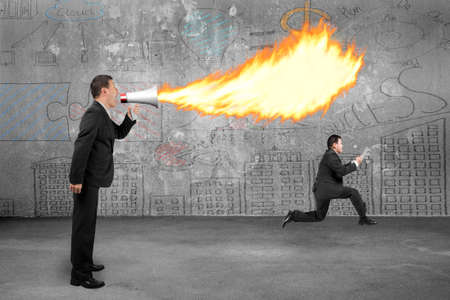 Angry boss using megaphone yelling to employee and spitting fire with business doodles concrete wall background