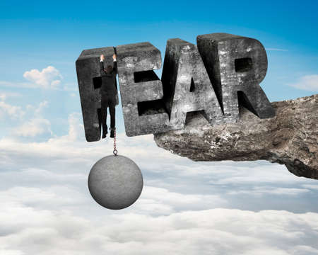 in bondage: Man shackled by heavy concrete ball hanging on big 3D fear mottled word at the edge of cliff with blue sky clouds background Stock Photo
