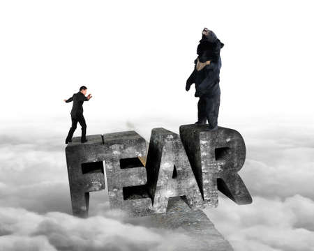 Businessman against black bear standing on fear 3D mottled concrete word, balancing on ridge with cloudy sky background Stock Photo