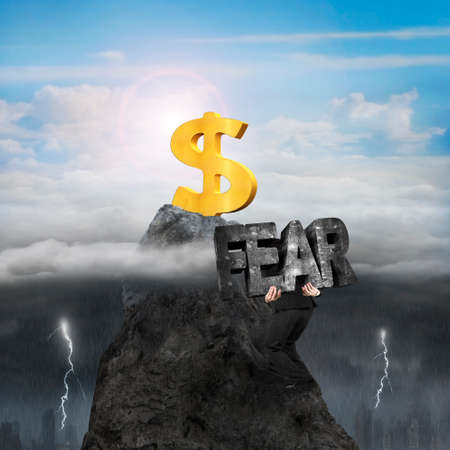 Man carrying 3d fear mottled concrete word, climbing toward golden dollar sign on mountain peak, with opposite weather conditions background, sunny sky cloudscape, dark overcast lightning raining cityscape
