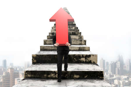 hard work ahead: Businessman carrying big 3D red arrow sign and climbing on old concrete stairs with urban scene background Stock Photo
