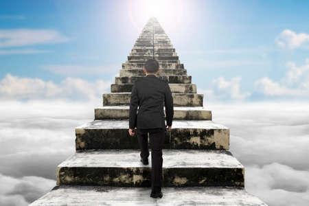 climbing stairs: Empresario subiendo por las viejas escaleras de hormig�n con cielo nubes luz del sol de fondo