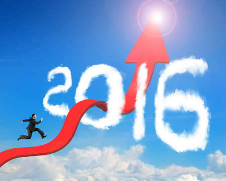 Businessman running on red arrow upward bending trend line breaking through 2016 shape clouds and blue sky sunlight background Banco de Imagens