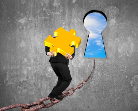 Man carrying golden jigsaw puzzle walking on old iron chain toward keyhole door with sky clouds view and gray concrete wall background photo