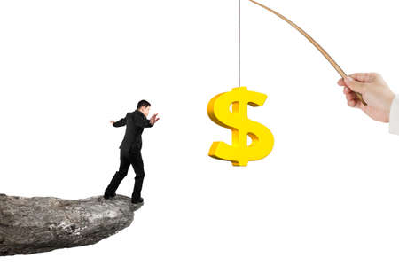 rod sign: Man balancing on rocky cliff for 3D golden dollar sign bait from fishing rod hand holding isolated on white background