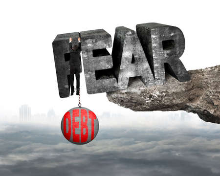 shackled: Man shackled by heavy red debt ball hanging on big 3D fear mottled concrete word at the edge of cliff with white background Stock Photo