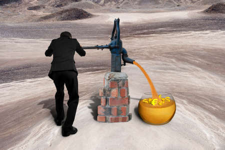 wealth concept: Man drawing out golden sand with 3D currency symbols from retro water pump on the desert background
