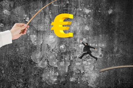 Man jumping for 3D golden euro symbol bait on fishing rod hand holding, with old mottled concrete wall background Stock Photo