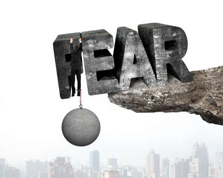 shackled: Man shackled by heavy concrete ball hanging on big 3D fear mottled word at the edge of cliff with urban scene background Stock Photo