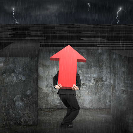 heavy rain: Man carrying big 3D red arrow up sign entering the huge maze with dark night heavy rain background