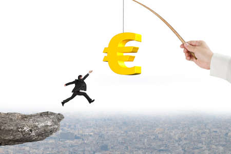control fraud: Man jumping for 3D golden euro symbol bait on fishing rod hand holding, with rocky cliff and urban scene background Stock Photo