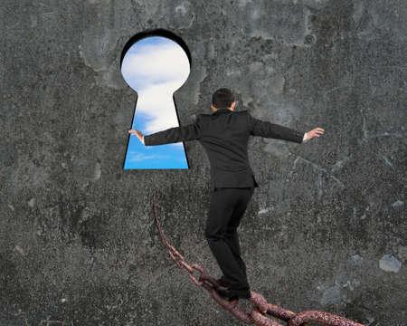 equilibrio: El hombre de equilibrio en la vieja cadena de hierro hacia el ojo de la cerradura, con vista al cielo y nubes de fondo gris muro de hormigón