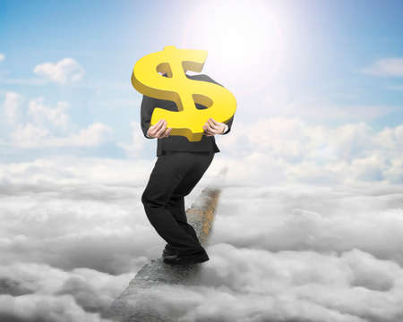 Businessman carrying big 3D gold dollar sign balancing on concrete ridge with sky cloudscape sunlight background photo