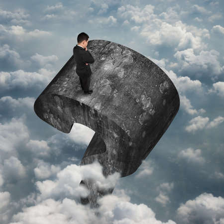 Man standing on top of huge 3D old concrete question mark with sky cloudscape background