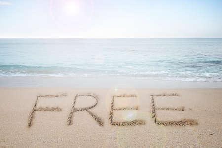 Free word handwritten in sand on sunny beach with sun sky sea background photo