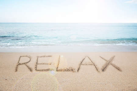 single word: Relax word handwritten in sand on sunny beach with sun sky sea background Stock Photo