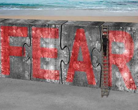 arduous: Businessman climbing ladder conquering huge puzzles concrete wall with red fear word, on sea beach background, overcoming fear concept. Stock Photo