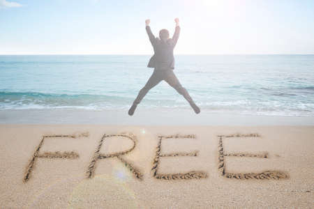 Jumping businessman cheering with free word handwritten in sand beach background Stock Photo