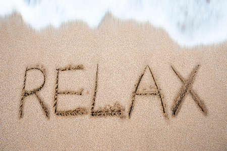 Relax word handwritten in sand on beach with white wave foam photo