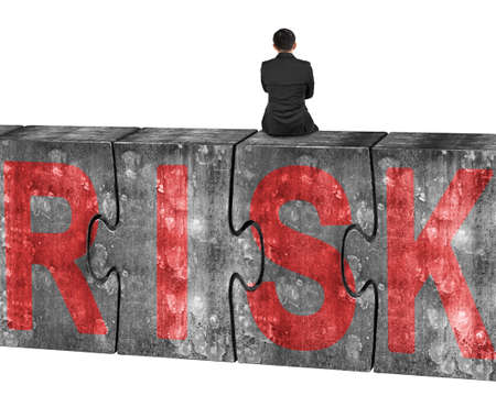 credit risk: Man sitting on four huge concrete puzzles with red risk word, isolated on white background Stock Photo