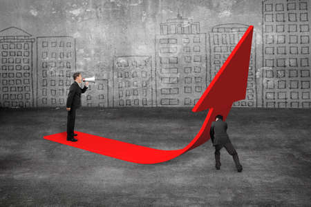 upward struggle: Manager using speaker yelling at businessman pushing red trend 3D arrow upward, with city buildings doodles wall background Stock Photo