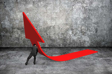 upward struggle: Man pushing red trend 3D arrow up with gray concrete indoor background