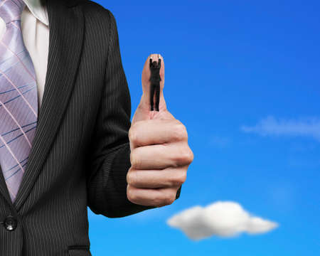 Businessman hanging on another big thumb with blue sky clouds background Stock Photo
