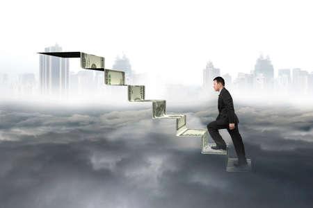 upward struggle: Man climbing on money stairs with city landscape gray cloudscape background Stock Photo