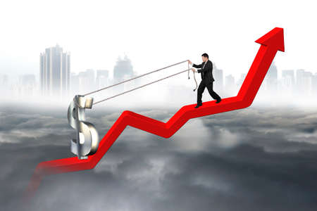 upward struggle: Business man pulling 3D dollar sign upward on red trend line with city landscape gray cloudscape background Stock Photo
