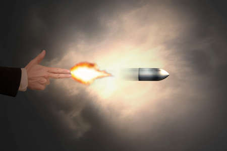 Male hand of gun gesture with firelight shooting the bullet photo