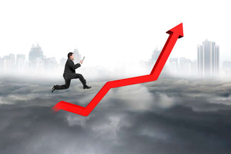 upward struggle: Business man holding tablet and jumping on red growth trend line with city landscape gray cloudscape background