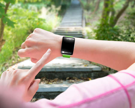 Sport woman finger pointing smart watch with blank black glass bent touchscreen, on forest trail background Stock Photo