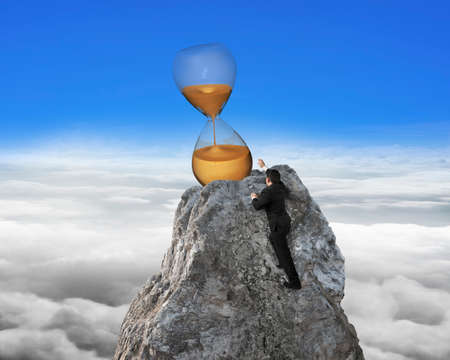hour glass: Businessman trying to grab hour glass on mountain peak, with blue sky cloudscape background.