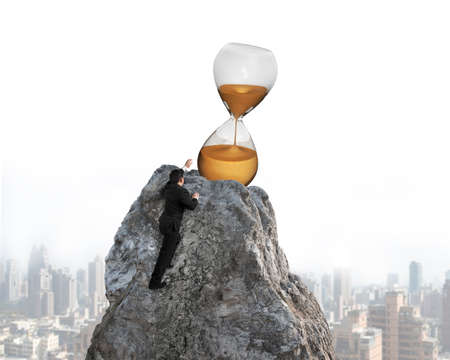 hour glass: Businessman trying to grab hour glass on mountain peak, with cityscape background.