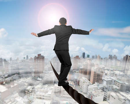 Businessman balancing on a wire with sky sun mist cityscape background.