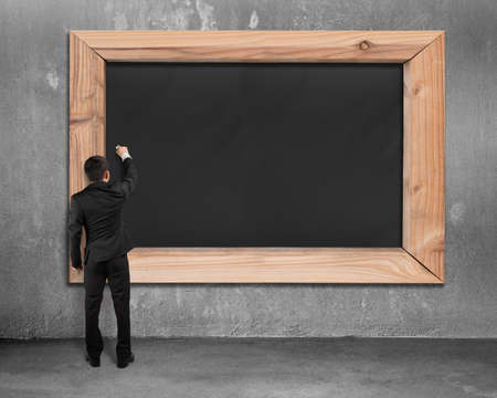 blank board: Businessman drawing on blank black chalkboard with gray concrete wall and floor background Stock Photo