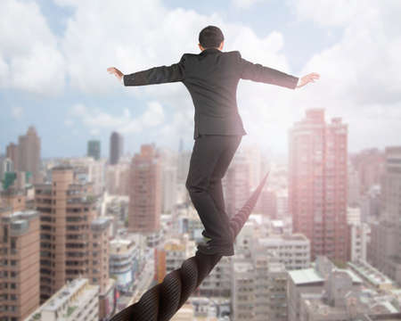 Businessman balancing on a wire with sky clouds cityscape background.