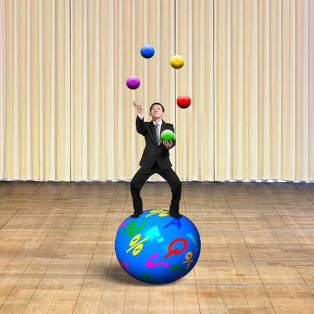 prioritizing: Businessman balancing on sphere juggling with balls, with indoor stage background.