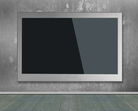 flat screen tv: Blank black wide flat TV screen hanging on concrete wall.